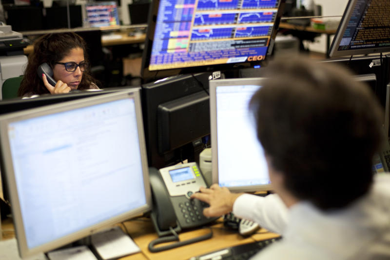 In this picture taken July 17 2013, brokers work in the trading room of a Portuguese bank during an auction of Portuguese Treasury Bills. The interest rate Portugal has to pay holders of its 10-year bonds, regarded as a reflection of investor confidence in the country, is around 6 percent. That is unaffordable for Portugal, though far better than the 17 percent that compelled Lisbon to ask for a bailout. (AP Photo/Armando Franca)