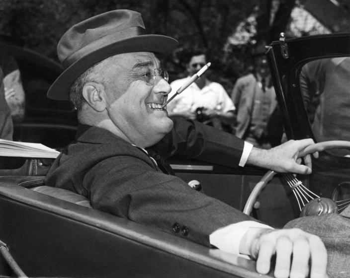 With a cigarette in a holder clenched in his teeth, Franklin D. Roosevelt sits jauntily at the wheel of his convertible in Warm Springs, Ga., in 1939. (Photo: Underwood Archives/Getty Images)