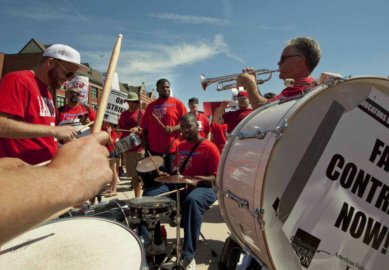 A band entertains a large group of public school teachers as they march past John Marshall Metropolitan High School on Wednesday, Sept. 12, 2012 in West Chicago. Teachers walked off the job Monday for the first time in 25 years over issues that include pay raises, classroom conditions, job security and teacher evaluations. (AP Photo/Sitthixay Ditthavong)
