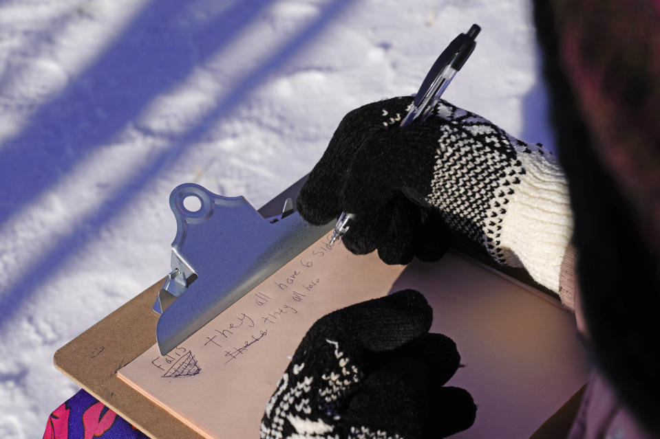 In this Monday, Dec. 8, 2020 photo, fourth grader Falis Asair makes notes while wearing gloves during an outdoor class at the Gerald Talbot School, in Portland, Maine. (AP Photo/Robert F. Bukaty)