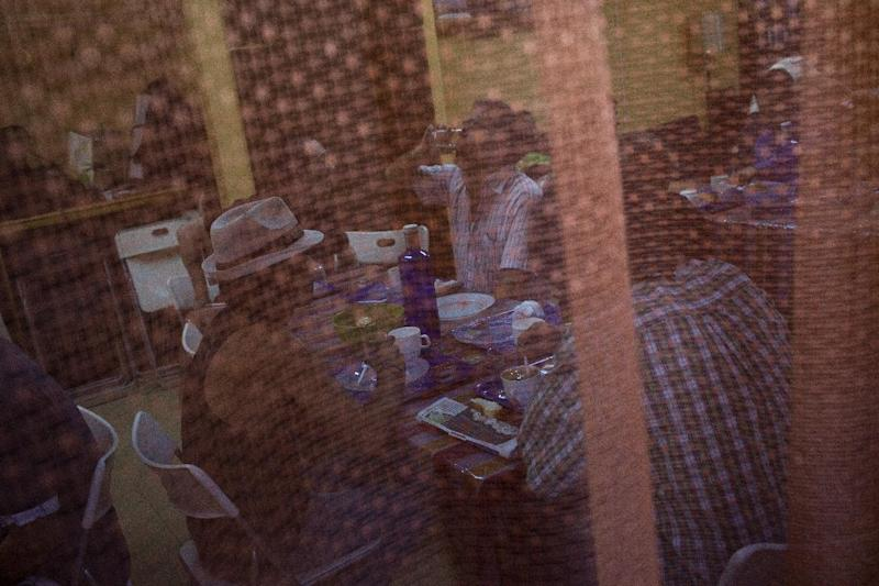 Men are seen through a curtain as they breakfast in Caliu, a charity site in Barcelona, Spain, Tuesday June 5, 2012. More than one hundred people are fed every day in Caliu as part of a charity program created by local volunteers and neighbors to help unemployed and people without financial resources. The Spanish economy is in recession for the second time in three years as the damage from a housing bust persists. Foreclosures are rising, Spain's banks are in worse financial shape and the government's deficit is hitting worrisome levels. (AP Photo/Emilio Morenatti)