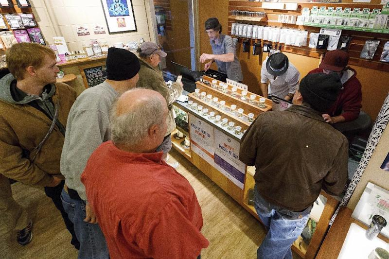 FILE - In this Oct. 1, 2015 file photo, employees of Amazon Organics, a pot dispensary in Eugene, Ore., help customers purchase recreational marijuana. Amid concerns of a federal crackdown lawmakers in Oregon are moving to protect the personal information of marijuana customers. (AP Photo/Ryan Kang, File)
