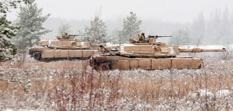 Two M1A2 Abrams Tanks providing security for Latvian and US troops during a live-fire training exercise, seen at the Adazi Training facility in Latvia, on November 21, 2014 (AFP Photo/-)