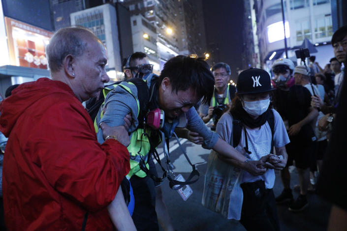 """A journalist is assisted after getting hit by pepper spray during a rally in Hong Kong on Sunday, Oct. 27, 2019. Hong Kong police fired tear gas Sunday to disperse a rally called over concerns about police conduct in monthslong pro-democracy demonstrations, with protesters cursing the officers and calling them """"gangster cops."""" (AP Photo/Kin Cheung)"""
