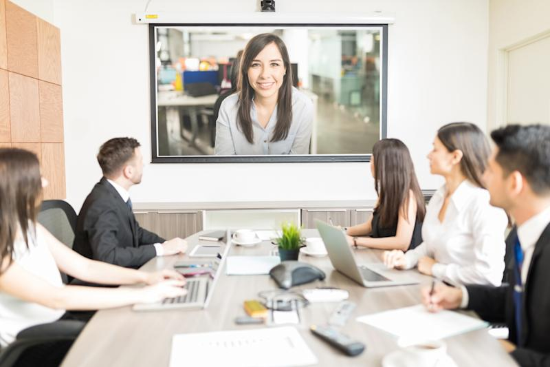 A group of business people gathered around a table looking at a screen, participating in a video conference.
