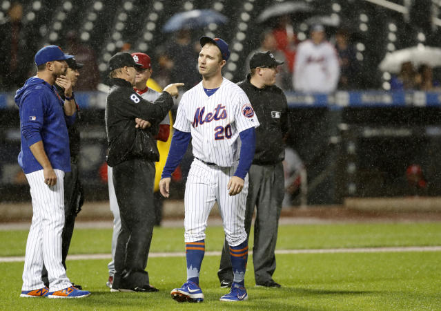 New York Mets manager Mickey Callaway, left, discusses field conditions with home plate umpire Mike Ripperger, second from left, and first base umpire Jeff Kellog (8) does the same with St. Louis Cardinals manager Mike Shildt during the ninth inning of a baseball game Thursday, June 13, 2019, in New York. Mets first baseman Pete Alonso (20) heads back to first. (AP Photo/Kathy Willens)