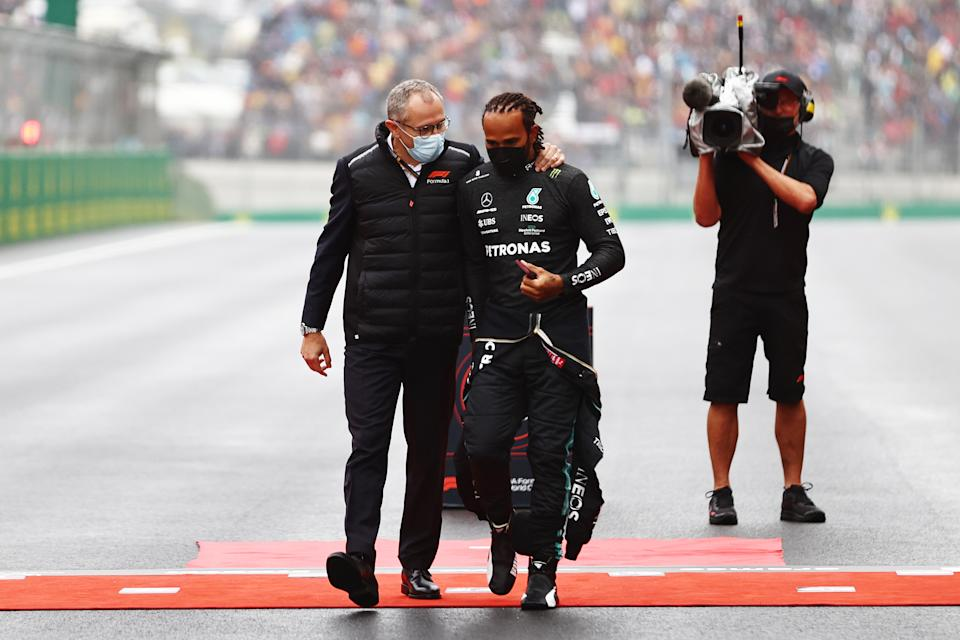 ISTANBUL, TURKEY - OCTOBER 10: Lewis Hamilton of Great Britain and Mercedes GP talks with Stefano Domenicali, CEO of the Formula One Group, on the grid during the F1 Grand Prix of Turkey at Intercity Istanbul Park on October 10, 2021 in Istanbul, Turkey. (Photo by Mark Thompson/Getty Images)