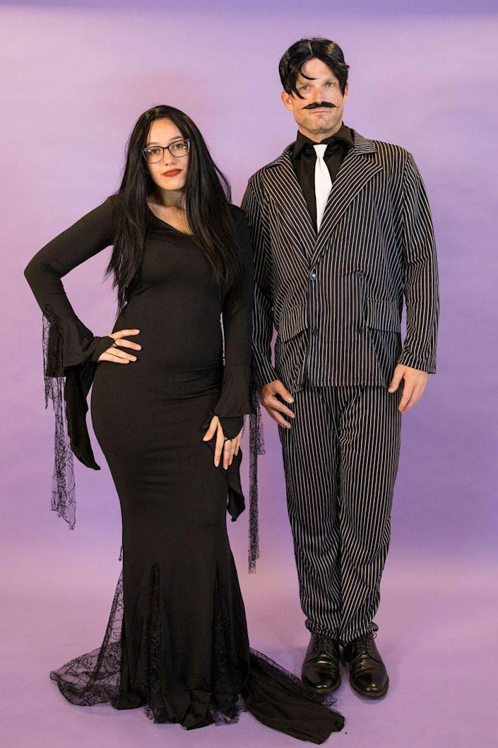 """<p>Dress up as the heads of the Addams household by donning a pinstripe suit and a long black dress.</p><p><a class=""""link rapid-noclick-resp"""" href=""""https://www.amazon.com/Zattcas-Womens-Vintage-Evening-X-Large/dp/B07XXXCKL8?tag=syn-yahoo-20&ascsubtag=%5Bartid%7C10070.g.1923%5Bsrc%7Cyahoo-us"""" rel=""""nofollow noopener"""" target=""""_blank"""" data-ylk=""""slk:SHOP BLACK DRESS"""">SHOP BLACK DRESS</a></p><p><a class=""""link rapid-noclick-resp"""" href=""""https://www.amazon.com/Forum-Novelties-Roaring-Pinstripe-Gangster/dp/B007FZHGIC?tag=syn-yahoo-20&ascsubtag=%5Bartid%7C10070.g.1923%5Bsrc%7Cyahoo-us"""" rel=""""nofollow noopener"""" target=""""_blank"""" data-ylk=""""slk:SHOP PINSTRIPE SUIT"""">SHOP PINSTRIPE SUIT</a></p>"""