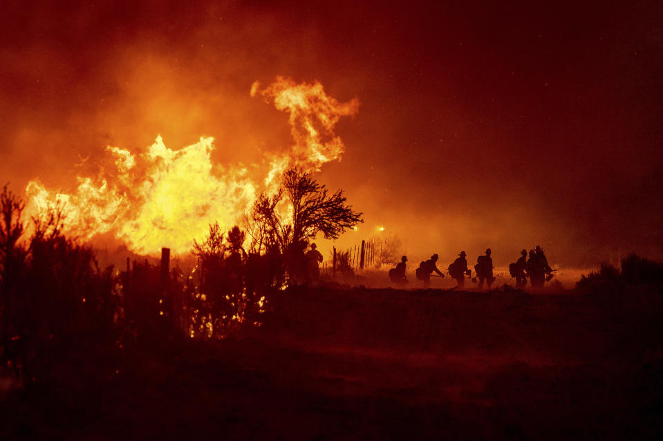 Firefighters battle the Sugar Fire, part of the Beckwourth Complex Fire, in Doyle, Calif., on Friday, July 9, 2021. (AP Photo/Noah Berger)