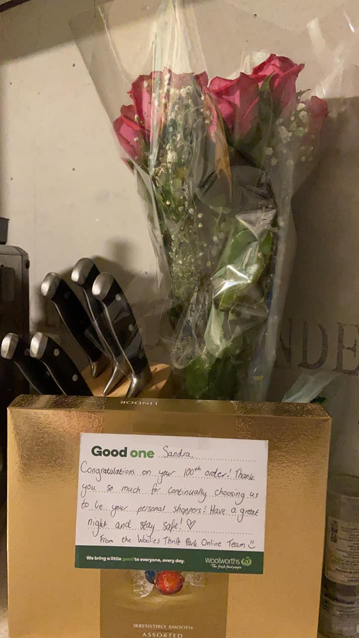 Woolworths customer shared a photo of the bunch of fresh pink roses and the box of chocolate she received as part of her 100th online order. Source: Facebook.