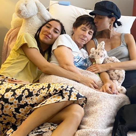 Jess and Lisa cuddle in bed with their mum, Colleen, who lives with a rare neurological condition