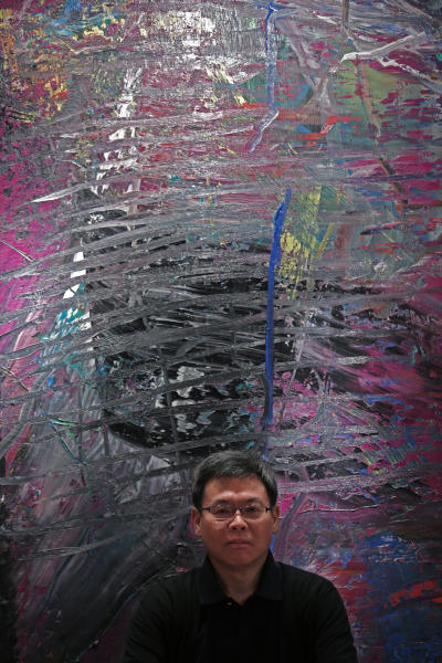 In this photo taken on Monday, April 2, 2012, Indonesian-Chinese farming tycoon Budi Tek poses in front of a paiting by Gerhard Richter during an auction preview in Hong Kong. Tek is set to open the De Museum in Shanghai next year featuring Asian and Western contemporary art, after opening his first in Indonesia's capital Jakarta in 2008. While Asia's new generation of wealthy are usually better known for splashing out on extravagant toys such as private jets, mega-sized yachts and supercars, some instead, have built big art collections and now aspire to showcase their refined sensibility to a wider audience. (AP Photo/Vincent Yu)
