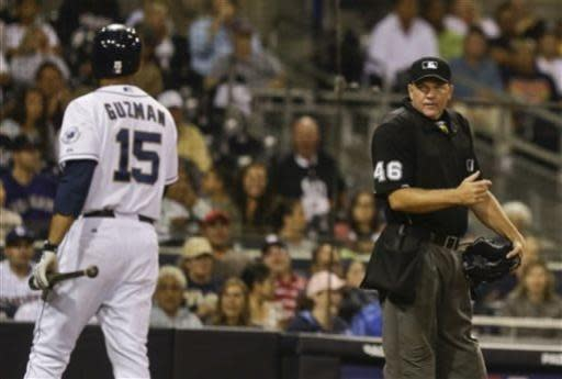 Home plate umpire Ron Kulpa stares at San Diego Padres' Jesus Guzman who walks around home plate after a strike two call by Kulpa in the seventh inning of a baseball game against the Colorado Rockies in San Diego, Wednesday, July 10, 2013. The pitch came with the tying run on base. Guzman struck out on the next pitch. (AP Photo/Lenny Ignelzi)