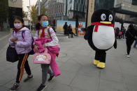 Children past by a mascot for Tencent during a promotion event in Beijing on Wednesday, Nov. 11, 2020. China is banning children from playing online games for more than three hours a week, the harshest restriction so far on the game industry as Chinese regulators continue cracking down on the technology sector. (AP Photo/Ng Han Guan)