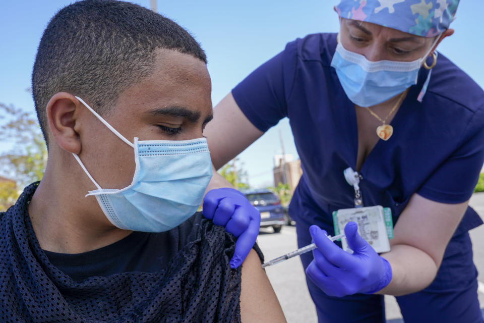 FILE In this May 14, 2021, file photo, Justin Bishop, 13, watches as Registered Nurse Jennifer Reyes inoculates him with the first dose of the Pfizer COVID-19 vaccine at the Mount Sinai South Nassau Vaxmobile parked at the De La Salle School in Freeport, N.Y. U.S. healthy officials say that most fully vaccinated Americans can skip testing for COVID-19, even if they were exposed to someone infected. (AP Photo/Mary Altaffer, File)