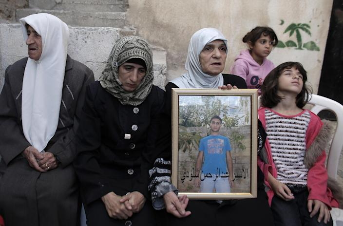 Family members of a Palestinian Abdelrahman Shaludi hold his portrait at their fhome in the east Jerusalem neighbourhood of Silwan, October 23, 2014 (AFP Photo/Ahmad Gharabli)