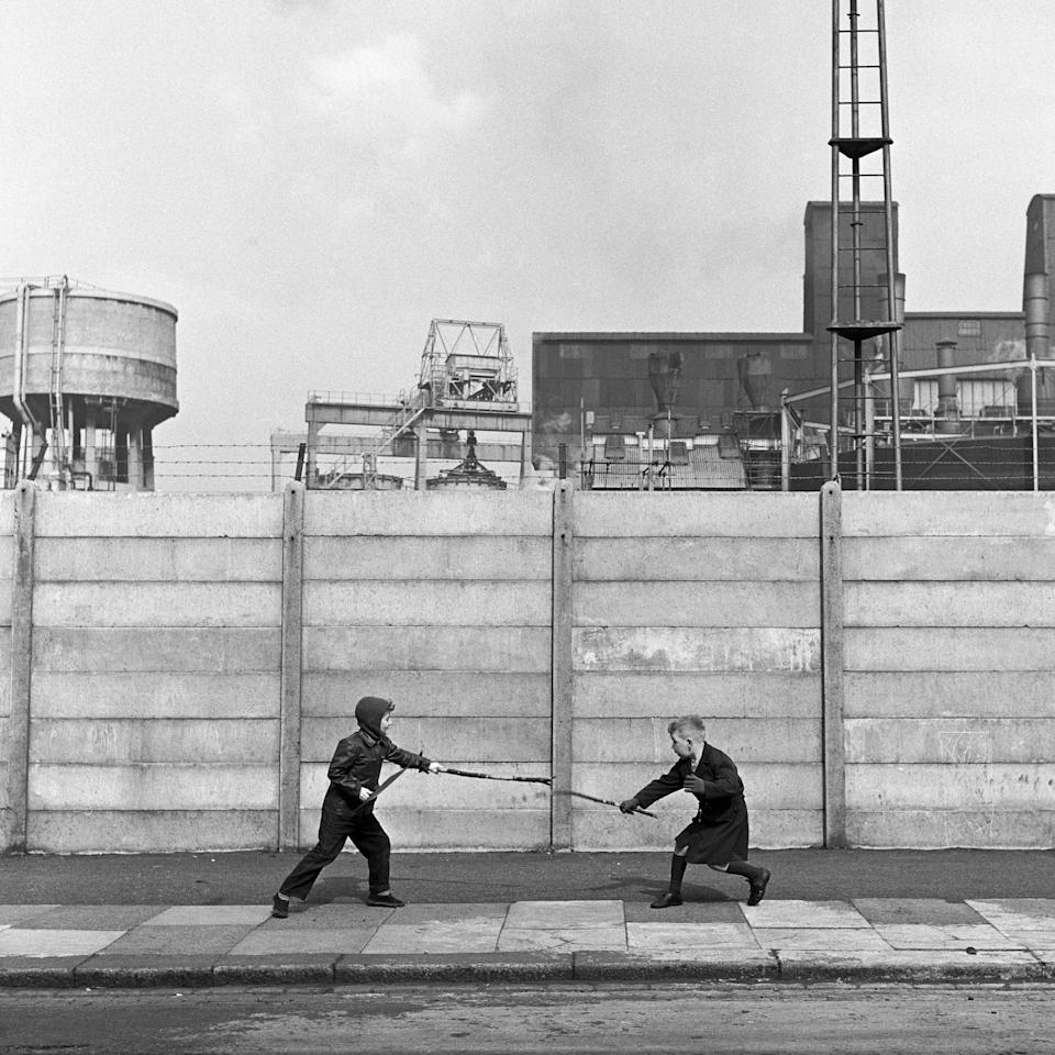 Two boys fighting with sticks in front of a concrete wall, London, UK, circa 1960. (Photo by Frederick Wilfred/Getty Images)  - Getty