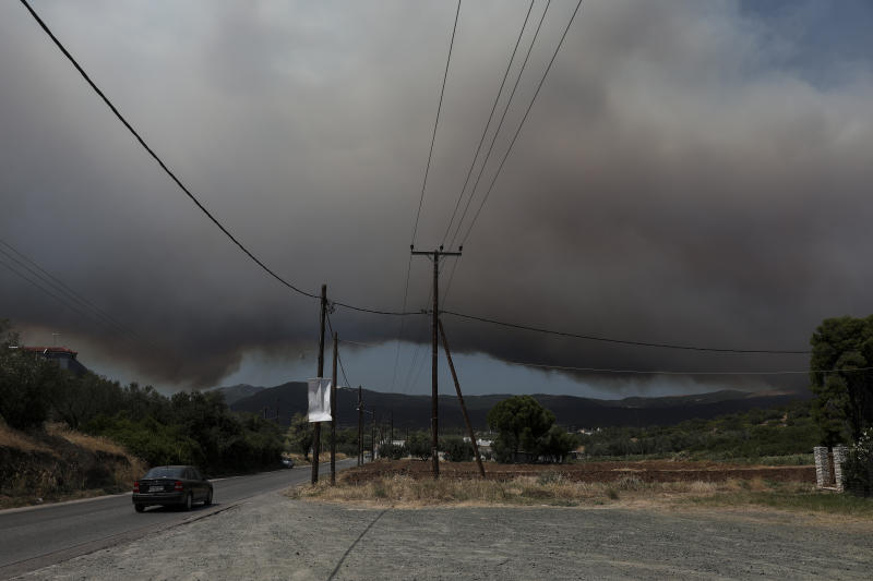 A cloud of smoke rises from a nearby forest fire at Psachna village on the island of Evia, northeast of Athens, Tuesday, Aug. 13, 2019. Dozens of firefighters backed by water-dropping aircraft are battling a wildfire on the island that has left the Greek capital blanketed in smoke. (AP Photo/Yorgos Karahalis)
