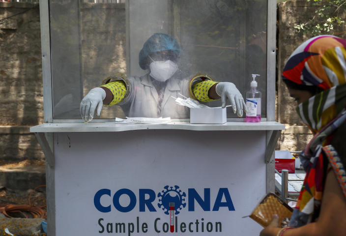 An Indian health worker takes a break between collecting swab samples for COVID-19 test in Hyderabad, India, Monday, May 3, 2021. (AP Photo/Mahesh Kumar A.)