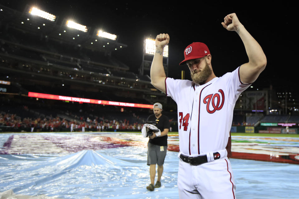 Washington Nationals Bryce Harper (34) bows his head and raise his arms with clenched fists as the Nationals celebrate and bid goodbye to their fans ending their last home game of the season with a 9-3 rain delayed win against the Miami Marlins in Washington, Wednesday, Sept. 26, 2018. (AP Photo/Manuel Balce Ceneta)