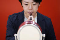 Naruhiko Ito, assistant brand manager of Brand Shiseido Group, demonstrates the brand's latest lip balm for men in Tokyo Thursday, April 15, 2021. A large personal care company, Shiseido, says one of its male makeup lines has seen double-digit growth during the coronavirus pandemic. Company officials give a similar reason: Men, confronted with the sight of their faces repeatedly during online meetings, want to improve what they see. (AP Photo/Eugene Hoshiko)