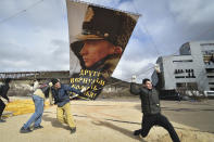 """People adjust a portrait of Russian President Vladimir Putin attached to a balloon during an anniversary celebration of the 2014 Crimean annexation, in Sevastopol, Crimea, Thursday, March 18, 2021. Residents of cities in Crimea and Russia are holding gatherings to commemorate the seventh anniversary of Russia's annexation of the Black Sea peninsula from Ukraine. The sign reads """"Another gave us back the cradle of baptism. March 18, 2014"""". (AP Photo)"""
