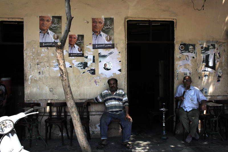 """Two Egyptian men sit under posters of presidential candidate Ahmed Shafiq at a traditional coffee shop during the second day of the presidential runoff in Cairo, Egypt Sunday, June 17, 2012. Egyptians are choosing between a conservative Islamist and Hosni Mubarak's ex-prime minister in a second day of a presidential runoff that has been overshadowed by the domination of the country's military. Arabic on the poster reads """"Ahmed Shafiq, President for Egypt, Egypt is for all."""" (AP Photo/Nasser Nasser)"""