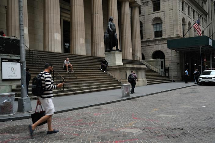 People walk along Wall Street in the Financial District. (Photo by Spencer Platt/Getty Images)