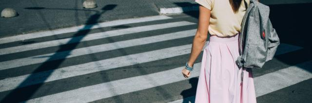 Rear view of young woman wearing pink skirt with backpack crossing the road at pedestrian crosswalk on sunny summer day.