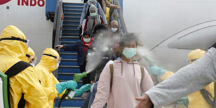 Indonesians arriving from Wuhan are sprayed with antiseptic at Hang Nadim Airport in Batam, Indonesia on February 2, 2020.