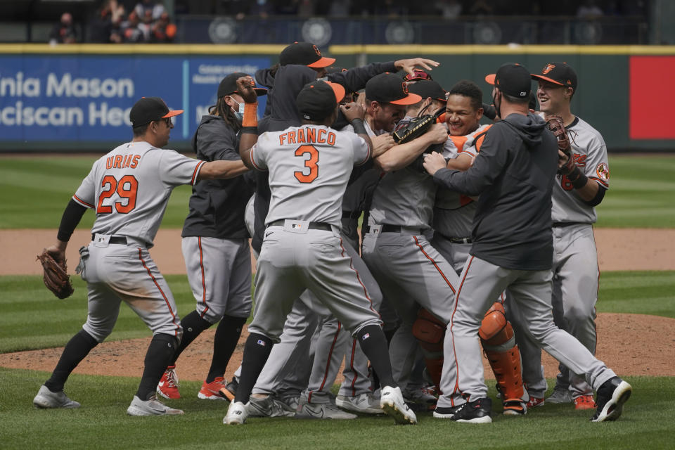 Baltimore Orioles starting pitcher John Means is mobbed by teammates after he threw a no-hitter in the Orioles' baseball game against the Seattle Mariners, Wednesday, May 5, 2021, in Seattle. The Orioles won 6-0. (AP Photo/Ted S. Warren)