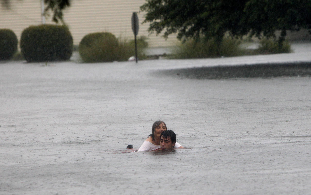 Garen Doll helps a woman through flood waters from Tropical Storm Debby in downtown Live Oak, Fla. on Tuesday, June 26, 2012. The National Hurricane Center says Debby has weakened to a tropical depression as it continues to move across Florida, bringing flooding to many areas. (AP Photo/The Gainesville Sun, Matt Stamey)