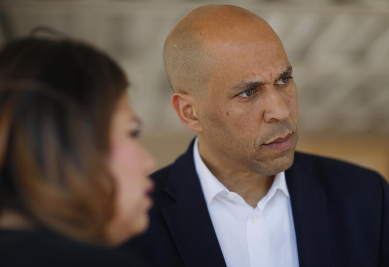 Democratic presidential candidate Sen. Cory Booker, right, speaks with Astrid Silva, left, and others after a round table with Dreamers and immigrant activists, Saturday, April 20, 2019, in Las Vegas. (AP Photo/John Locher)