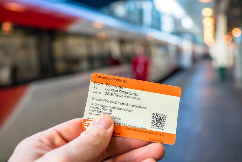 Edinburgh, UK - Close-up of a train ticket from Edinburgh to London King's Cross, with the train waiting on the platform at Edinburgh's Waverley station in the background.