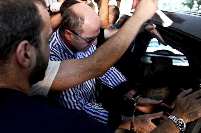 Members of the media gather around former head of the anti-terror department of the Istanbul police, Ali Fuat Yilmazer (L) as he leaves a hospital in Istanbul after a medical check-up at the start of his custody in Istanbul on July 22, 2014 (AFP Photo/Ozan Kose)
