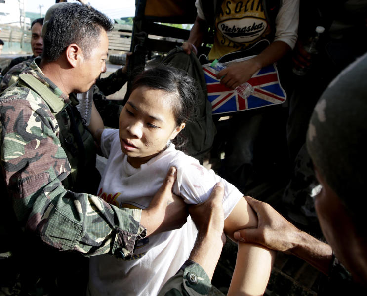 A hostage arrives for processing after being released from the hands of Muslim rebels in Zamboanga city, southern Philippines Tuesday Sept. 17, 2013. About 64 hostages were freed or escaped during military operations early Tuesday, followed by another 14 who walked to freedom in separate batches. That brought to 116 the number of those rescued in the last 18 hours, said military spokesman Lt. Col. Ramon Zagala. The standoff, which began Monday when about 200 Moro National Liberation Front guerrillas stormed several coastal communities in Zamboanga city and seized several residents, has displaced more than 80,000, hundreds of homes razed to the ground, forced the closure of businesses and resulted in more than 50 deaths so far. (AP Photo/Bullit Marquez)