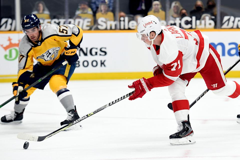 Red Wings center Dylan Larkin moves the puck in front Predators defenseman Dante Fabbro during the first period on Tuesday, March 23, 2021, in Nashville, Tennessee.