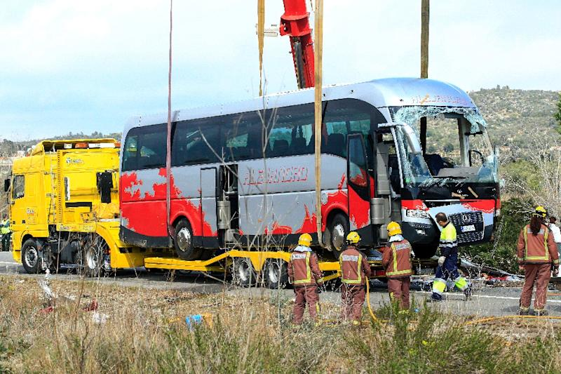 Emergency personnel standby as a crane loads a damaged bus onto a semi-trailer on the Spanish AP-7 motorway near Freginals, following a fatal bus accident that claimed the lives of 14 foreign students an injured 43 others early on March 20, 2016 (AFP Photo/Pau Barrena)