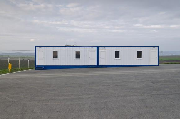 A white modular building with blue trim in a parking lot.