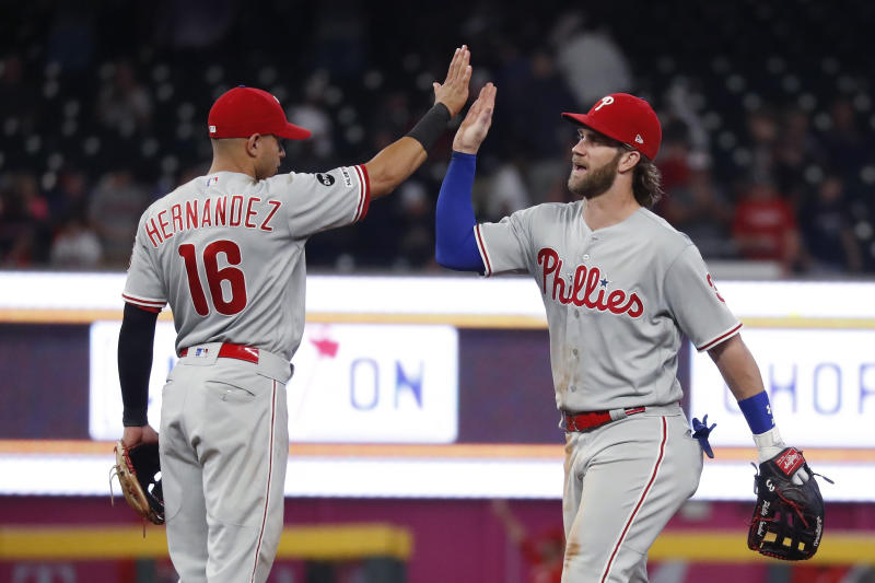 Philadelphia Phillies right fielder Bryce Harper, right, and second baseman Cesar Hernandez celebrate after the Phillies defeated the Atlanta Braves 5-4 in a baseball game Tuesday, Sept. 17, 2019, in Atlanta. (AP Photo/John Bazemore)