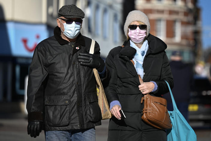 MERTHYR TYDFIL, WALES - NOVEMBER 06: A man and woman wearing face masks and sunglasses walk through the town centre on November 6, 2020 in Merthyr Tydfil, Wales. Merthyr Tydfil, with 741 cases per 100,000 people in the past week, has moved above Oldham and Blackburn in Lancashire as the worst-hit area in the UK. Wales is currently in a 'firebreak' lockdown which started on October 23 and will end on November 9. (Photo by Matthew Horwood/Getty Images)