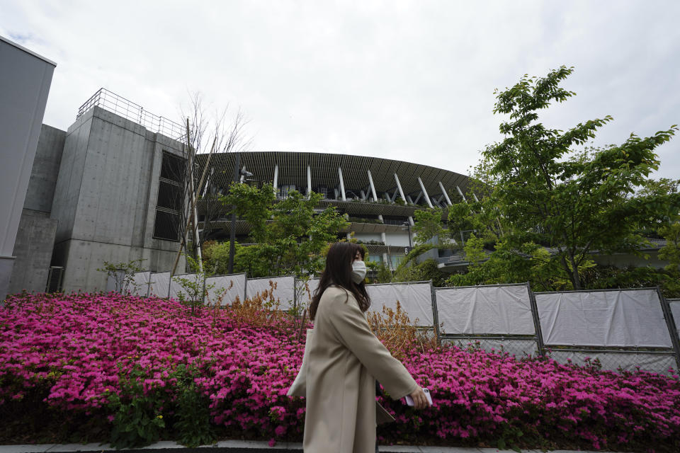A woman wearing a protective mask to help curb the spread of the coronavirus walks near the Japan National Stadium, where opening ceremony and many other events are planned for postponed Tokyo 2020 Olympics Tuesday, April 6, 2021, in Tokyo. Many preparations are still up in the air as organizers try to figure out how to hold the postponed games in the middle of a pandemic. (AP Photo/Eugene Hoshiko)