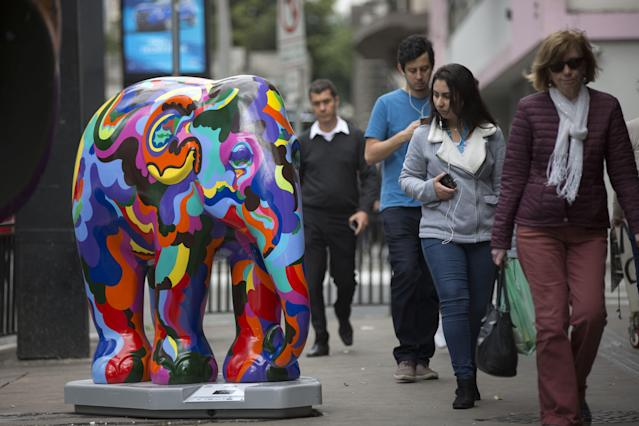 <p>Passer-by look on an elephant sculpture as part of the 'Elephant Parade' at the Paulista Avenue in Sao Paulo, Brazil, Aug. 1, 2017. (Photo: Sebastiao Moreira/EPA/REX/Shutterstock) </p>