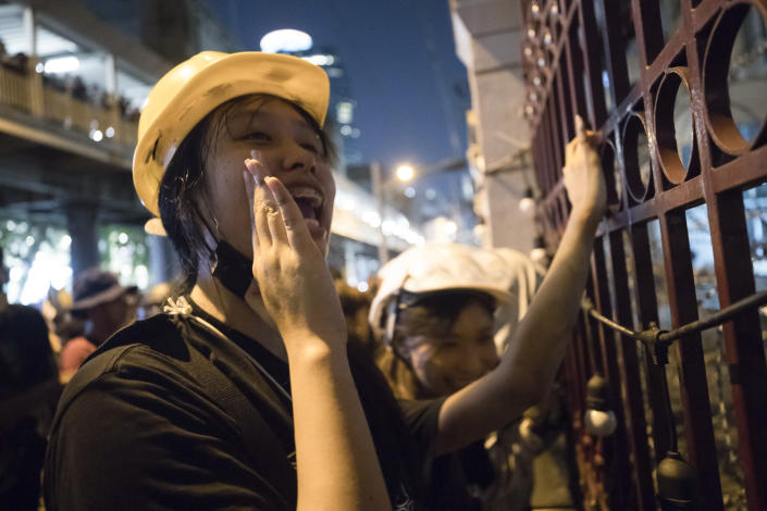 Pro-democracy protesters shout slogans outside Police headquarters during a rally in Bangkok, Thailand, Wednesday, Nov. 18, 2020. Police in Thailand's capital braced for possible trouble Wednesday, a day after a protest outside Parliament by pro-democracy demonstrators was marred by violence that left dozens of people injured. (AP Photo/Wason Wanichakorn)