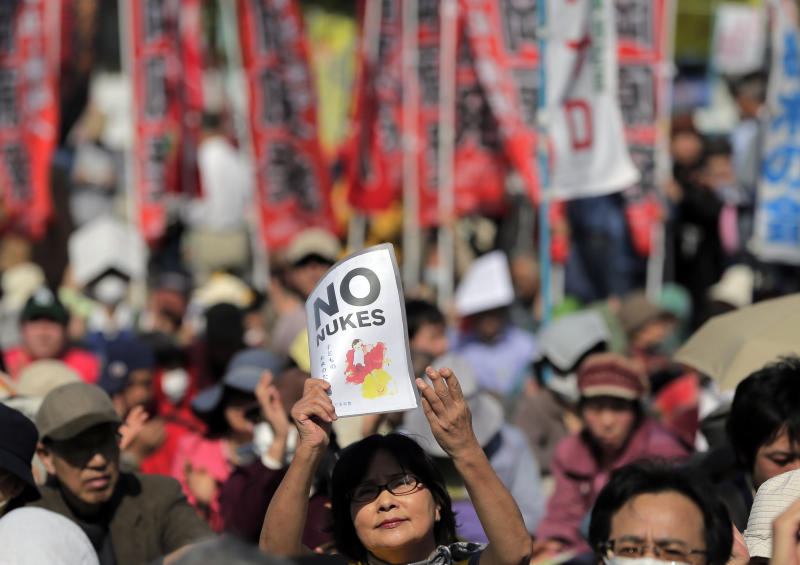 A protester holds aloft an anti-nuclear power plant sign as they stage a rally at a park in Tokyo, Saturday, March 9, 2013. Thousands of people rallied in a Tokyo park Saturday, demanding an end to atomic power, and vowing never to give up the fight, despite two years of little change after the nuclear disaster in Fukushima, northeastern Japan. (AP Photo/Itsuo Inouye)