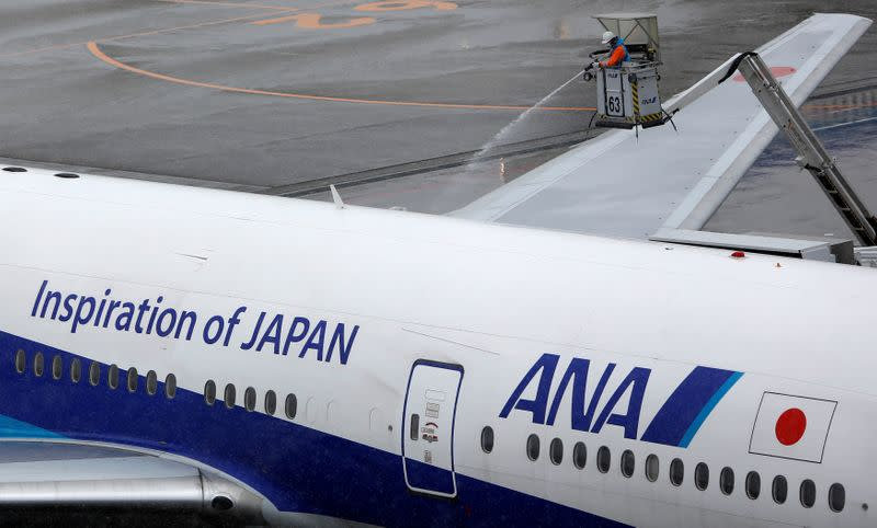 FILE PHOTO: A man works near an All Nippon Airways' (ANA) air plane parked at Haneda airport in Tokyo