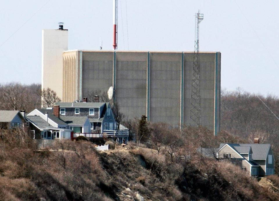 A portion of the Pilgrim Nuclear Power Station sits beyond houses along the coast of Cape Cod Bay in Plymouth, Mass.