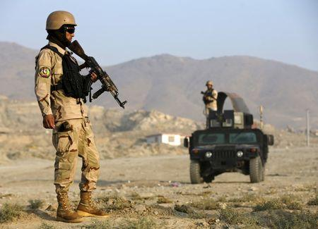Afghan policemen stand guard at a checkpoint in Deh Sabz district, Kabul, Afghanistan