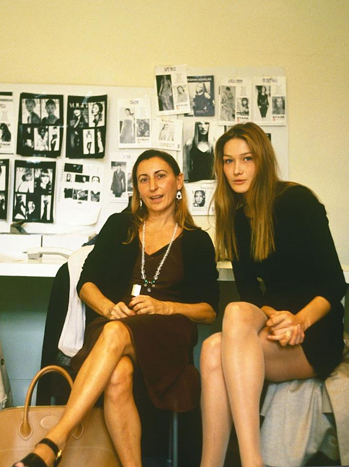 <p>The Italian-French supermodel was an early muse for Prada. One of the highest paid models of the '90s, Bruni walked numerous Prada runways and starred in multiple campaigns. Here, the two sit together during a 1994 fitting. </p>