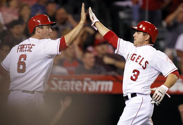 Los Angeles Angels' J.B. Shuck (3) congratulates David Freese (6) as both score on a single by Howie Kendrick in the fifth inning of a baseball game against the Cleveland Indians on Tuesday, April 29, 2014, in Anaheim, Calif. (AP Photo/Alex Gallardo)
